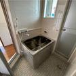追炊き付のお風呂。壁はパネルで、掃除しやすくなっています。右の扉を開けると小さなバルコニーがあります。
